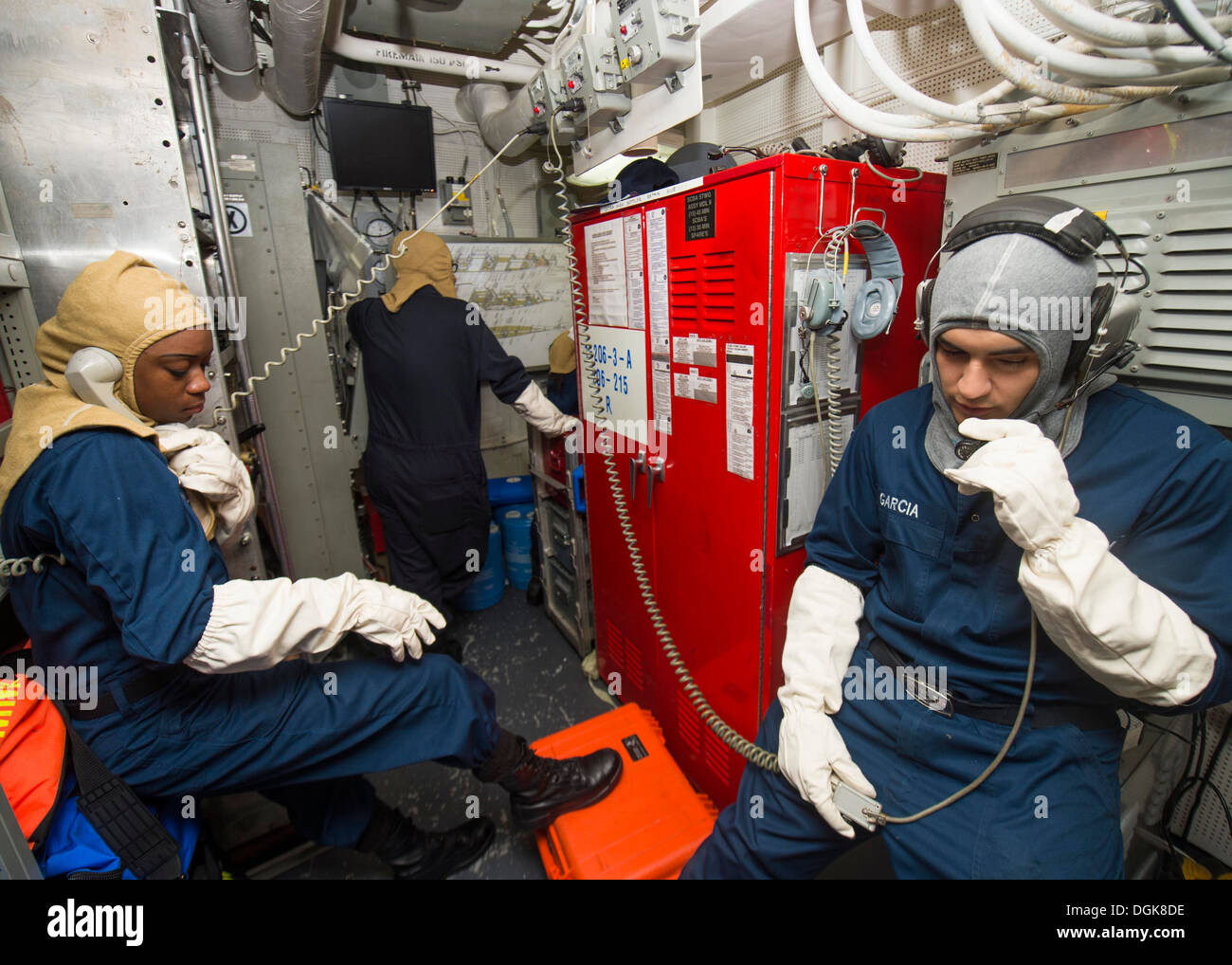 Ship's Serviceman Seaman Christopher Garcia, right, and Ship's Serviceman Seaman Naomi Dunkley serve as phone talkers during a general quarters drill aboard the Arleigh Burke-class guided-missile destroyer USS Mustin (DDG 89). Mustin is on patrol with the - Stock Image