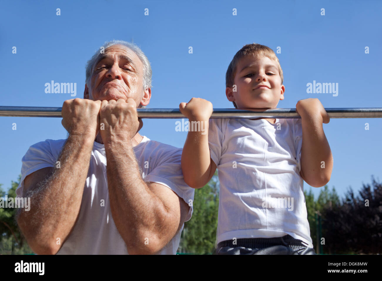 Man and grandson doing chin-ups - Stock Image
