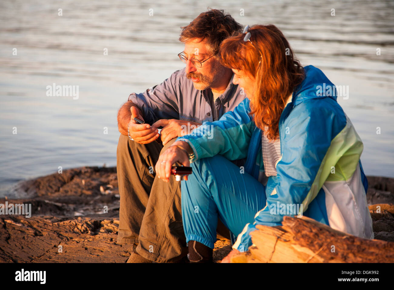 Mature couple sitting lakeside with mobile phones, Bath, Maine, USA - Stock Image