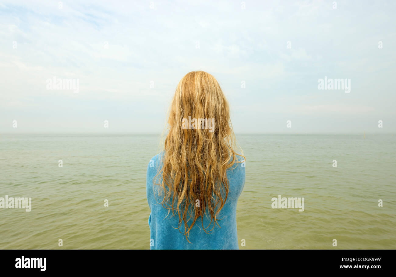 Backview of girl looking out at ocean - Stock Image