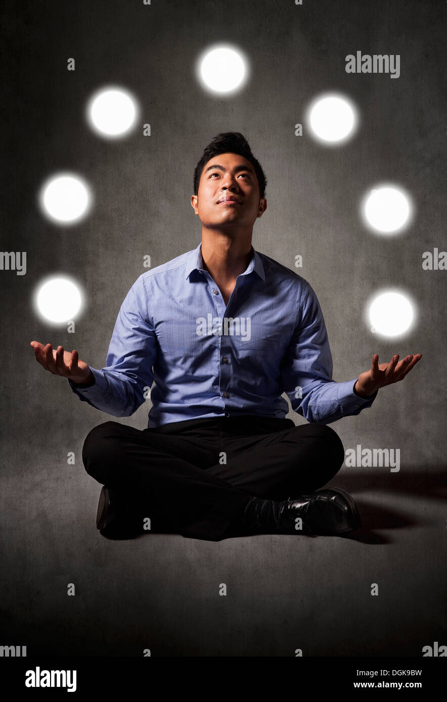 Businessman juggling balls of light Stock Photo