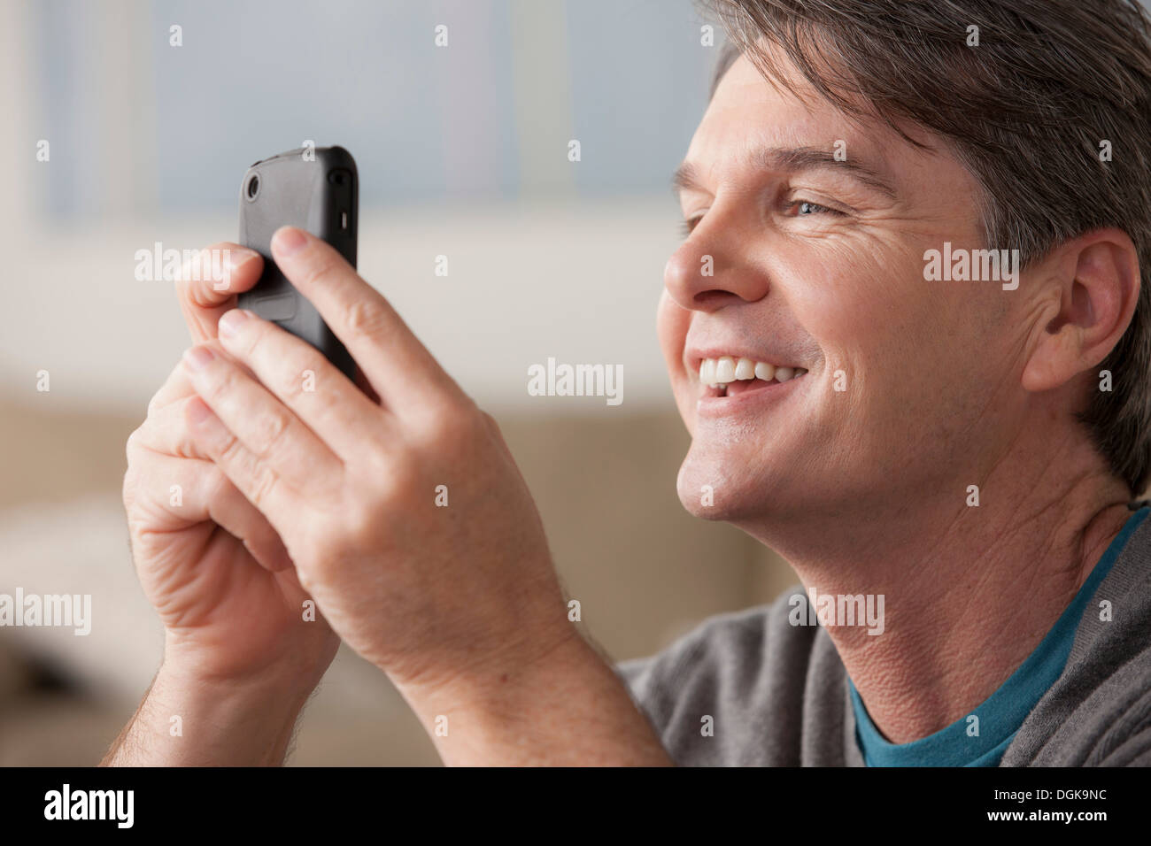 Mature man using cell phone - Stock Image