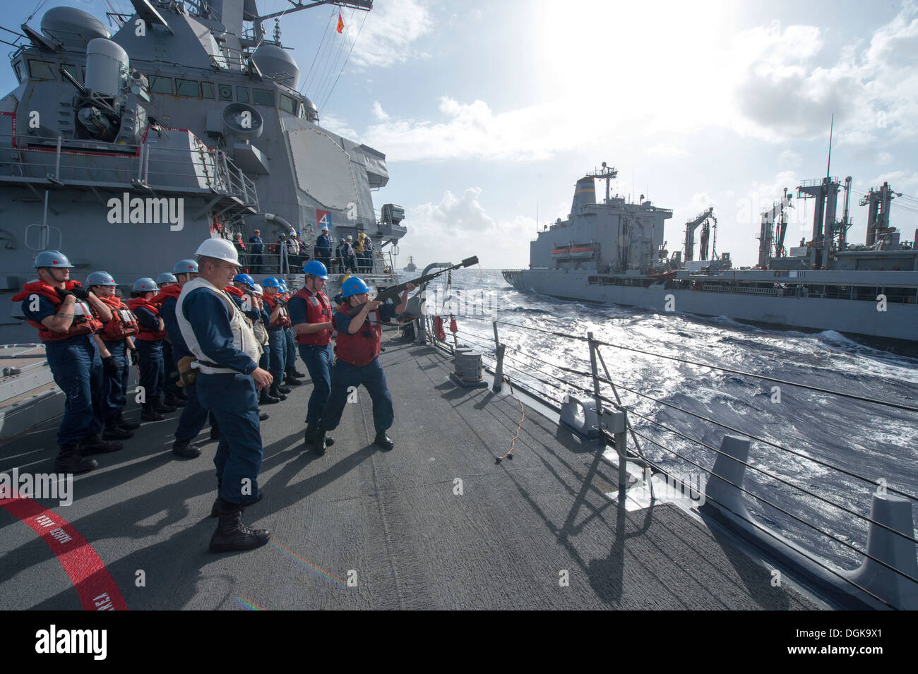 Gunner's Mate 2nd Class Whitney Gutierrez fires a shot line from the Arleigh Burke-class guided-missile destroyer USS Stout (DD - Stock Image