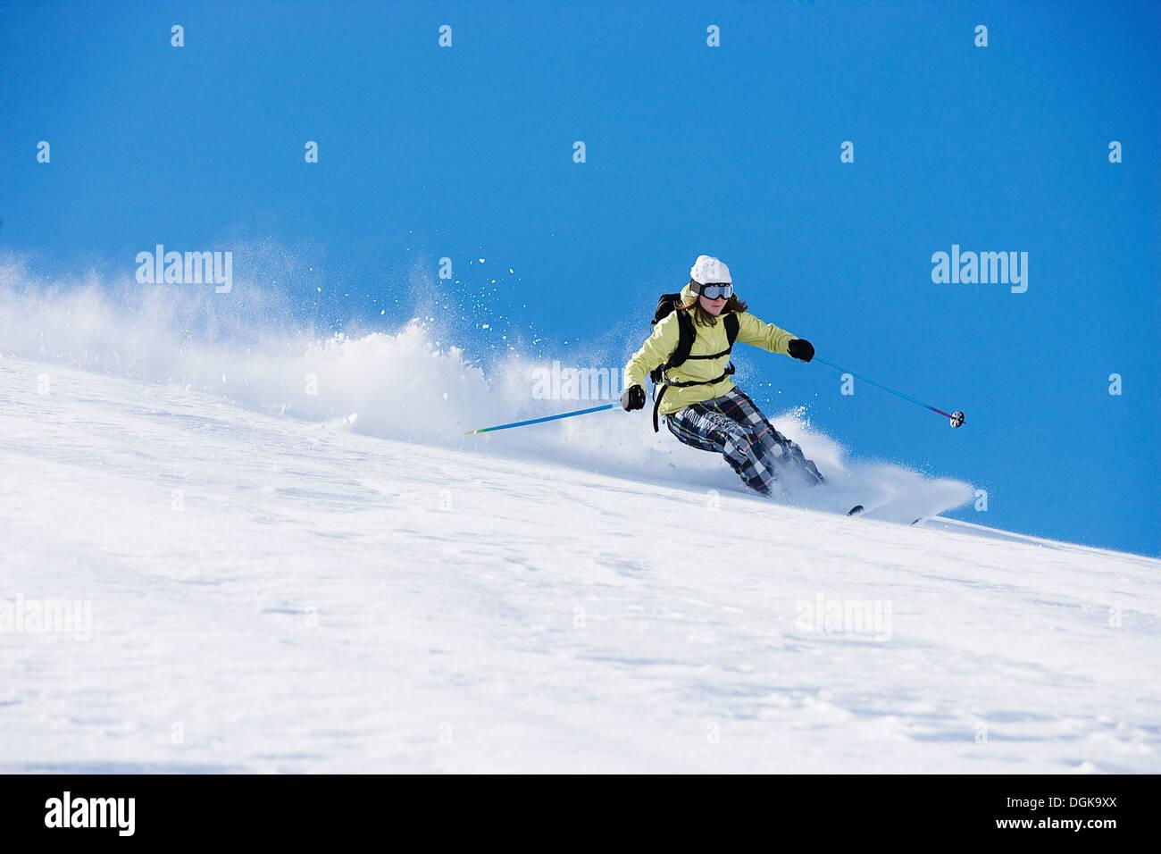 Female skiing down ski run - Stock Image