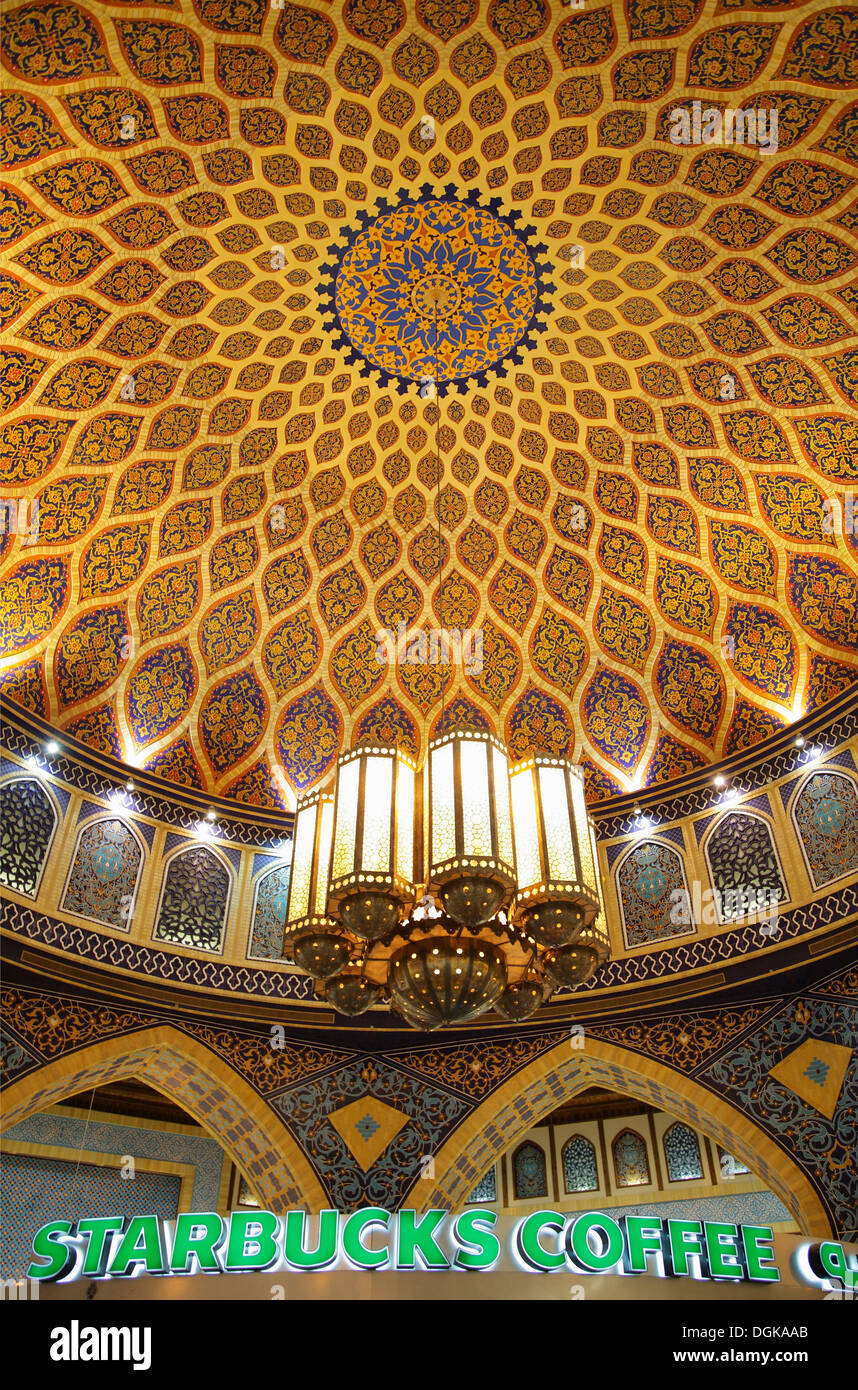 A traditional Iranian dome contrasts against a Starbucks in the Ibn Batutta mall. - Stock Image