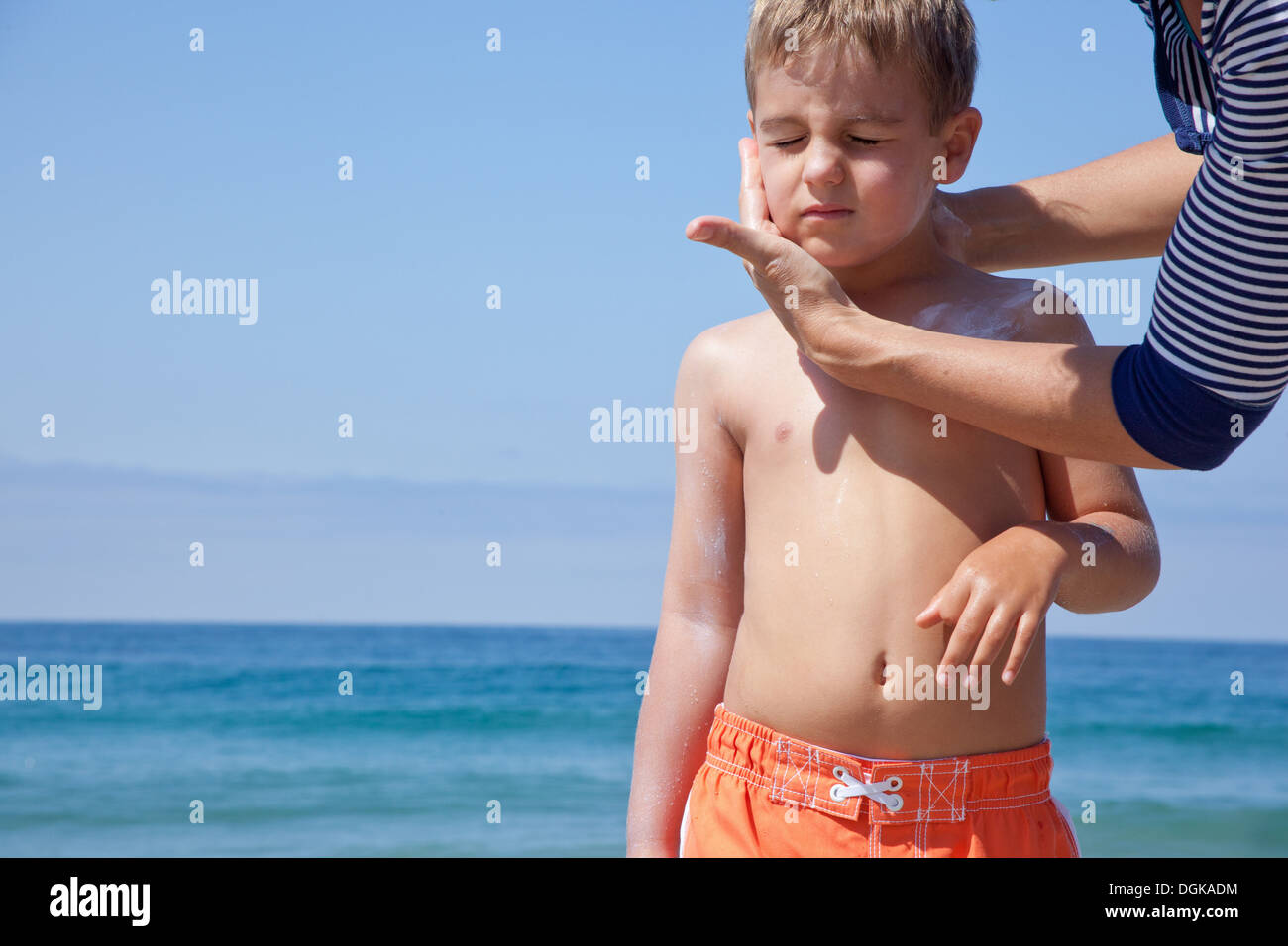 Mother applying sun cream to sons face at beach - Stock Image