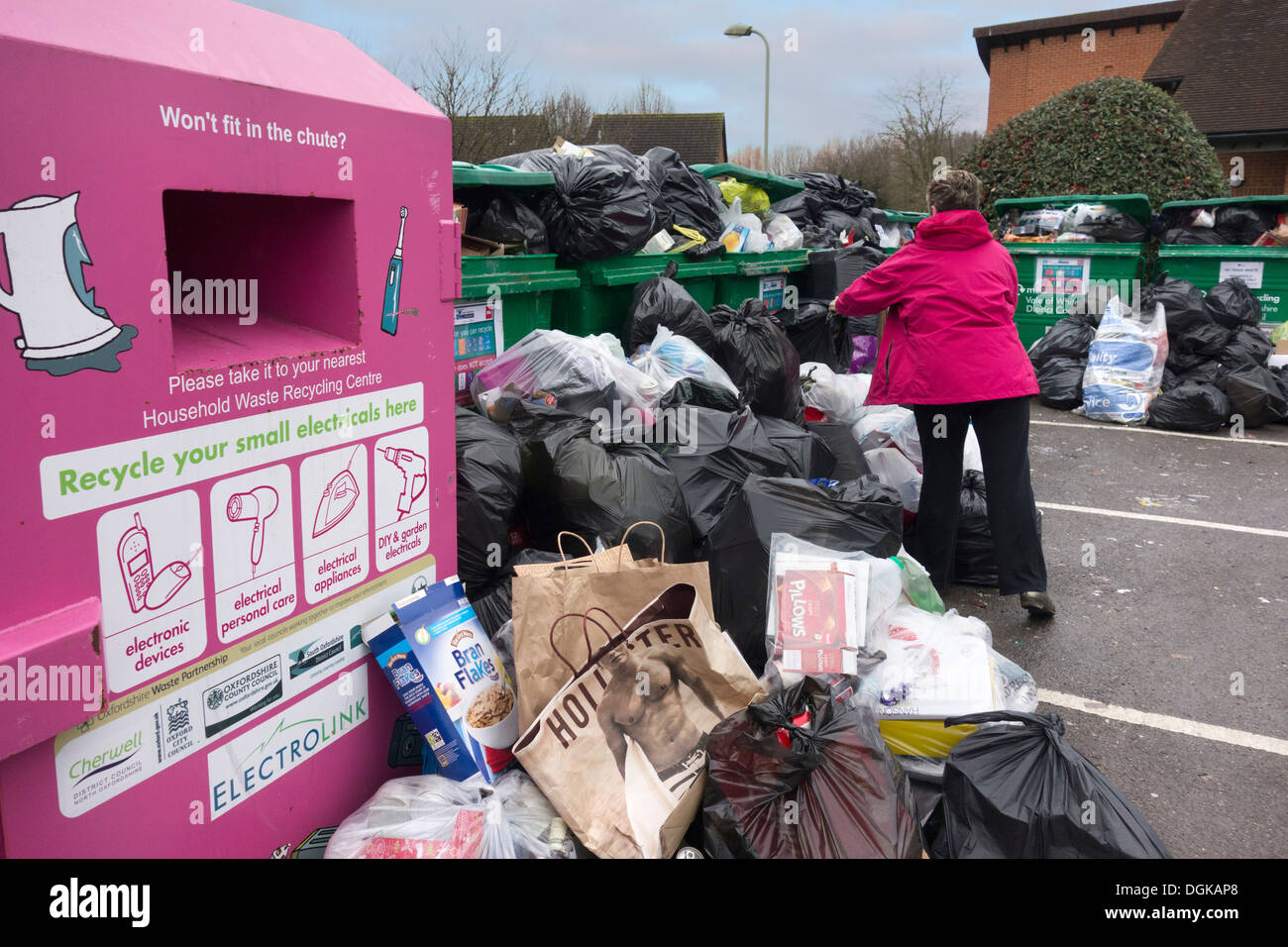 Woman discarding garbage at an overflowing waste recycling point at Peachcroft Housing Estate in Abingdon. - Stock Image