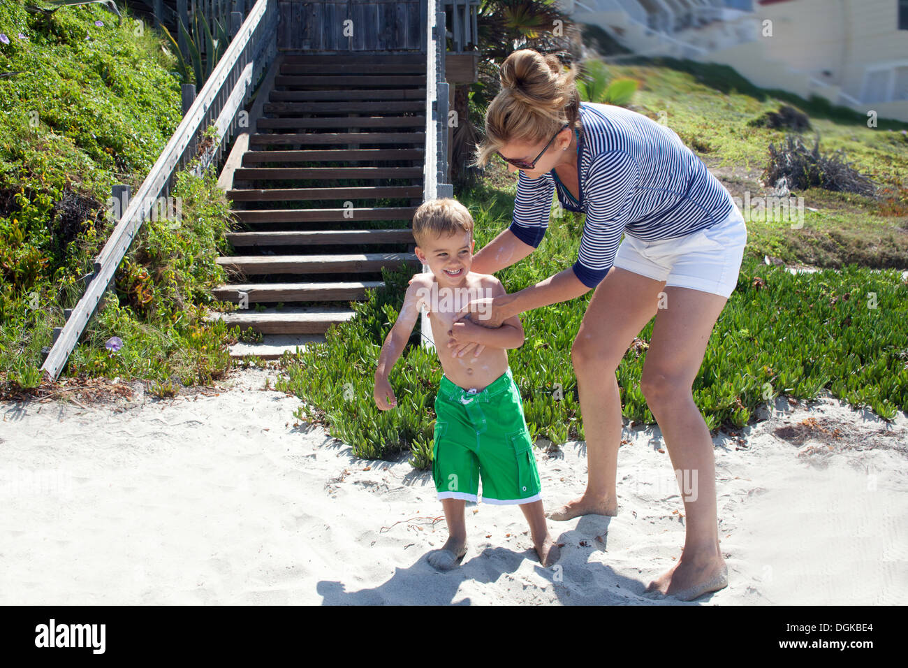 Mother applying sun cream to toddler at beach - Stock Image