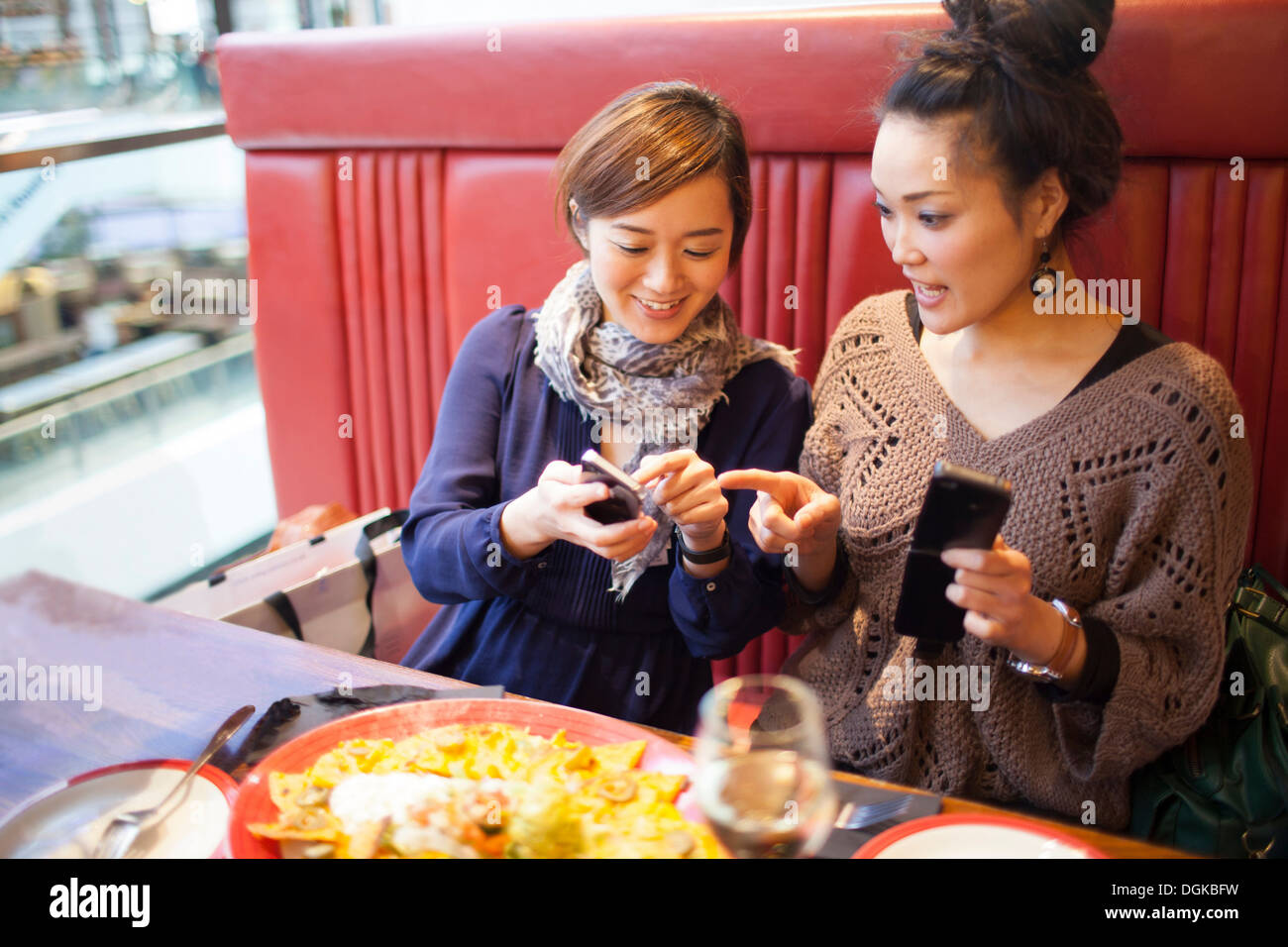 Young women using cell phones in restaurant - Stock Image