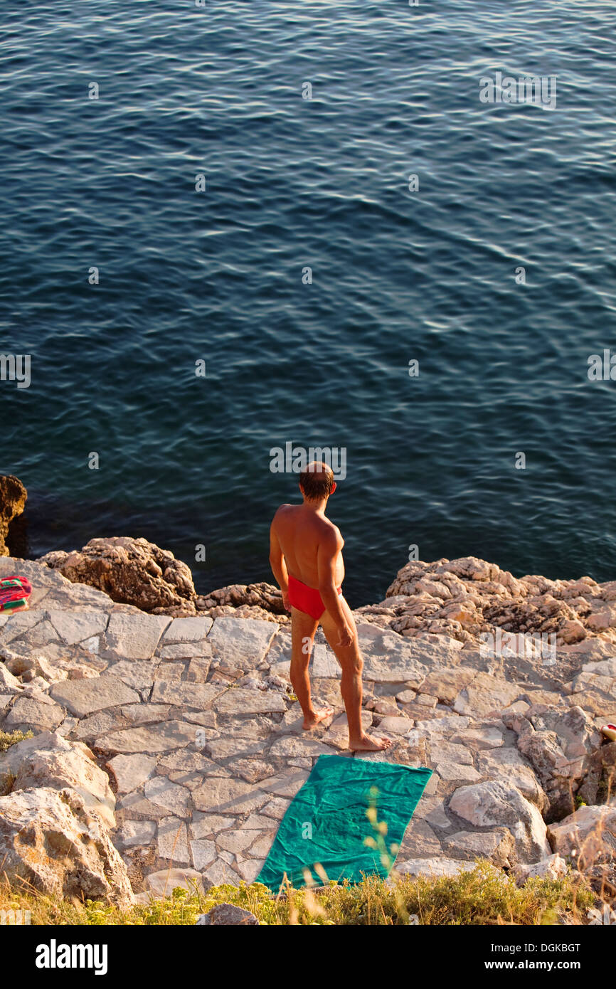 A sunbather looking out to sea on the Istrian coast. - Stock Image