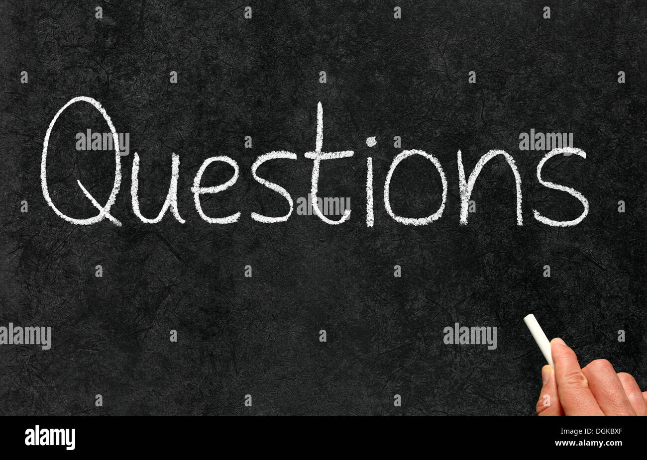 Questions word written with white chalk on a blackboard. - Stock Image