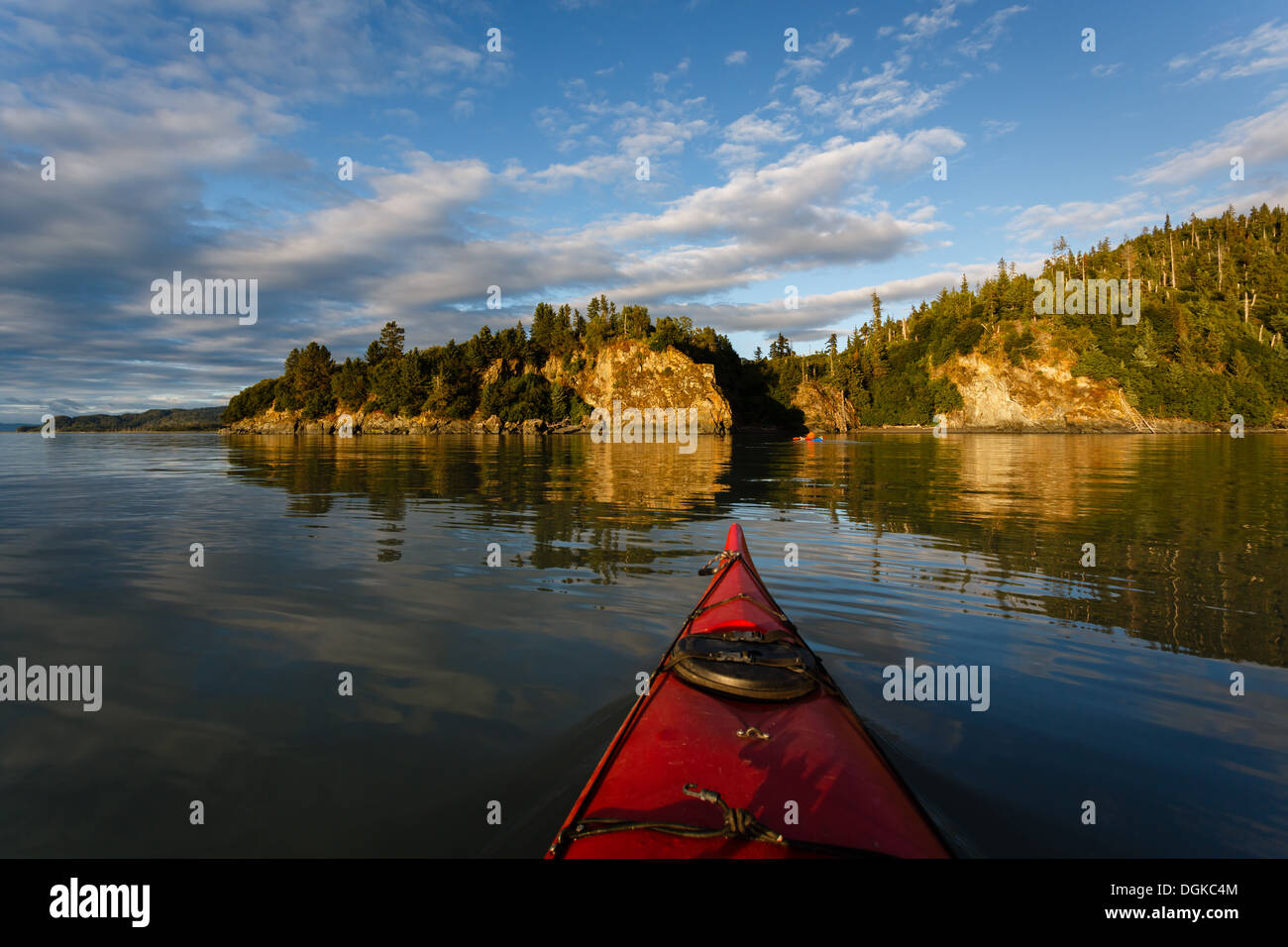 Kayak paddler heads toward land in remote Alaskan wilderness on sunny afternoon in summer - Stock Image