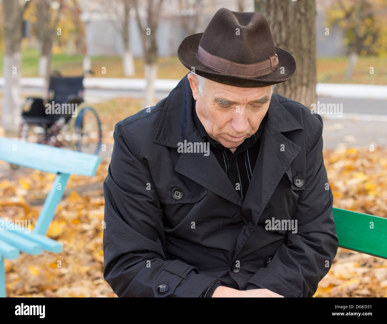 Close up portrait of a sad lonely old man on a park bench sitting with his head down and a despondent expression warmly dressed - Stock Image