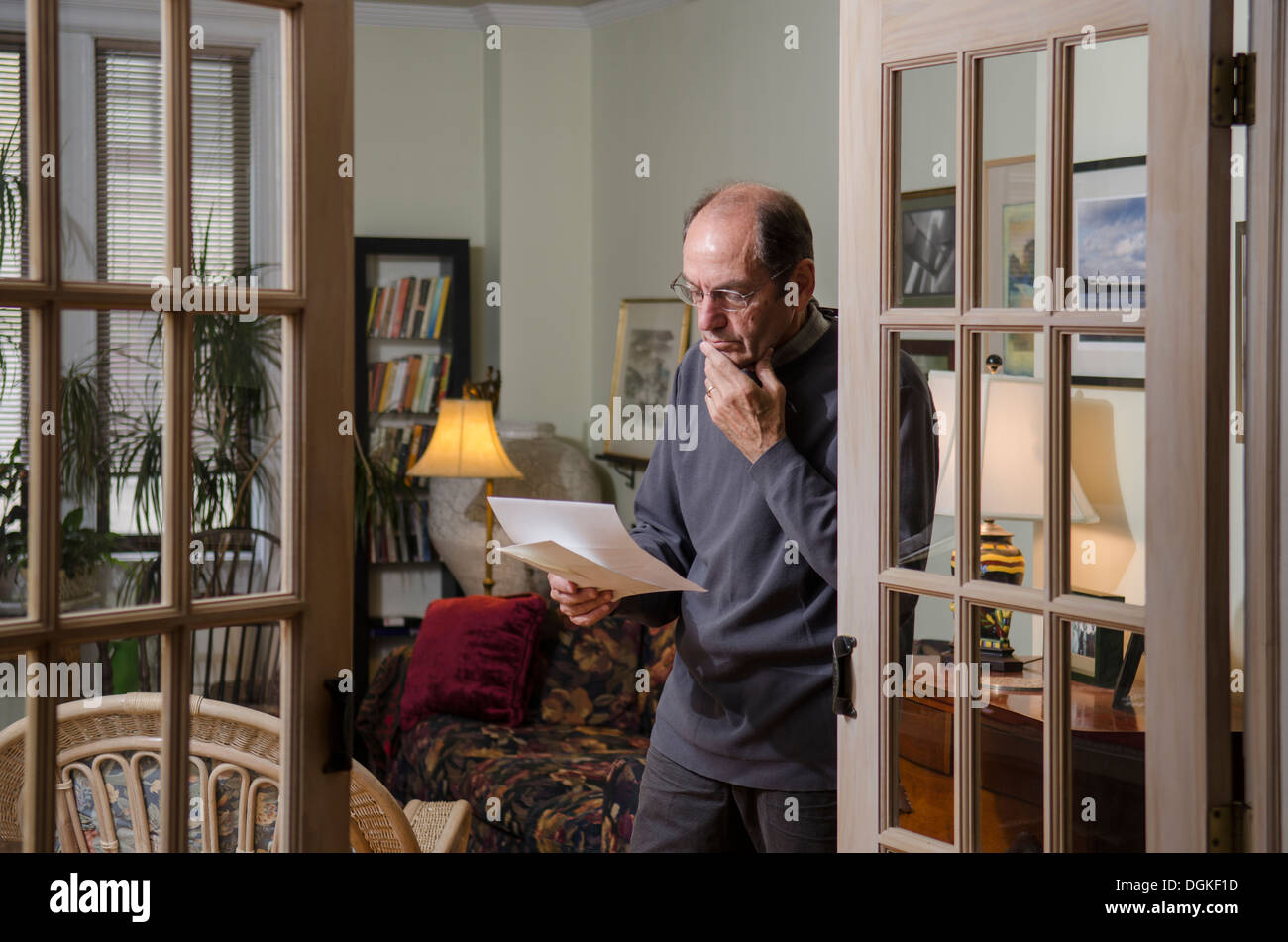 serious man reading letter at home - Stock Image