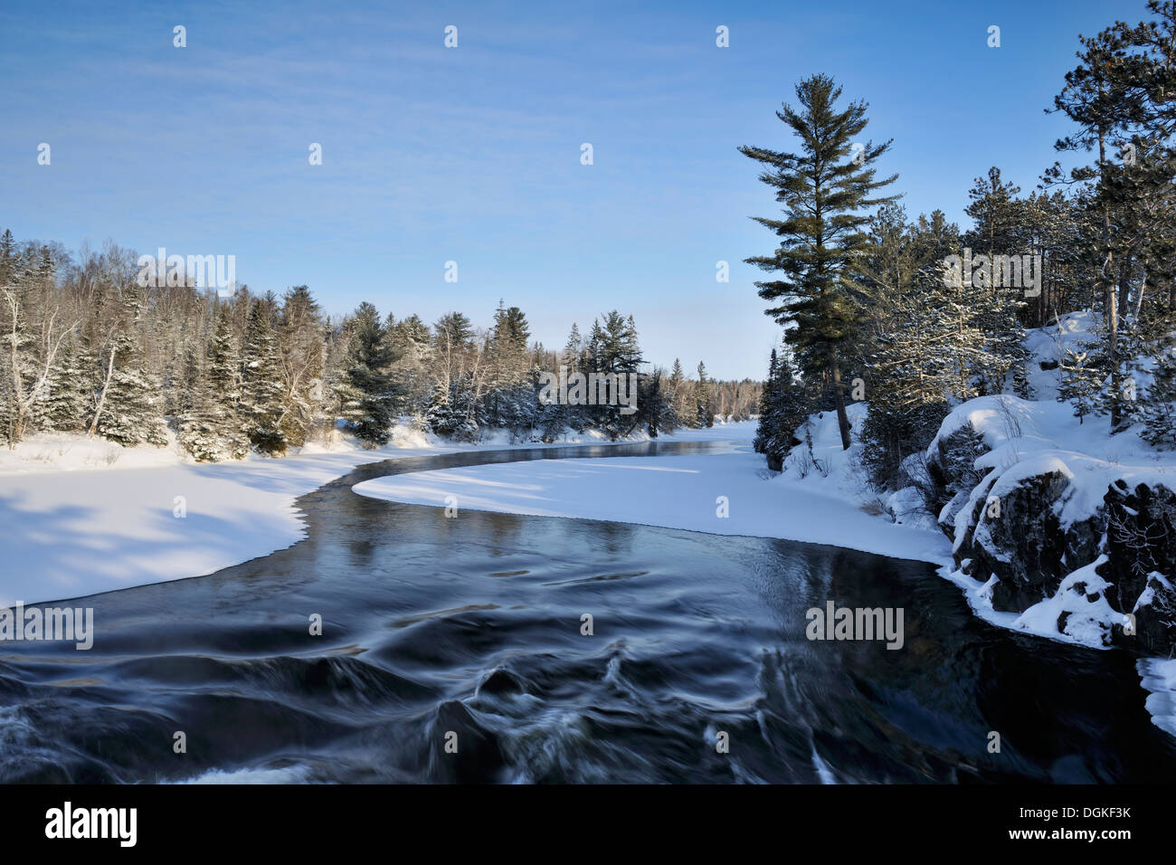 Open water of Wanapitei River and frosted pine trees in winter Wanup Ontario Canada - Stock Image