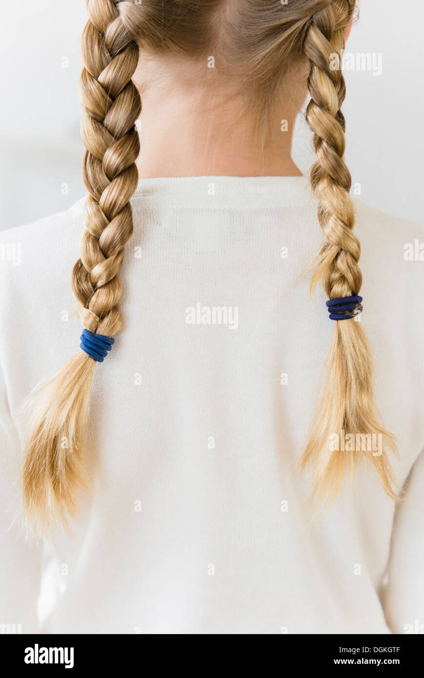 Rear view of girl (8-9) with plaits - Stock Image