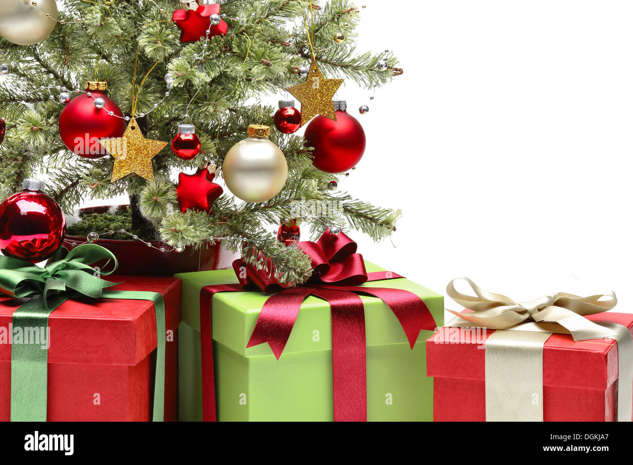 Decorated Christmas tree and gifts on white background - Stock Image