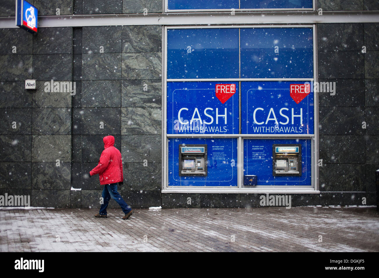 A man in a red jacket passes cash machines. - Stock Image