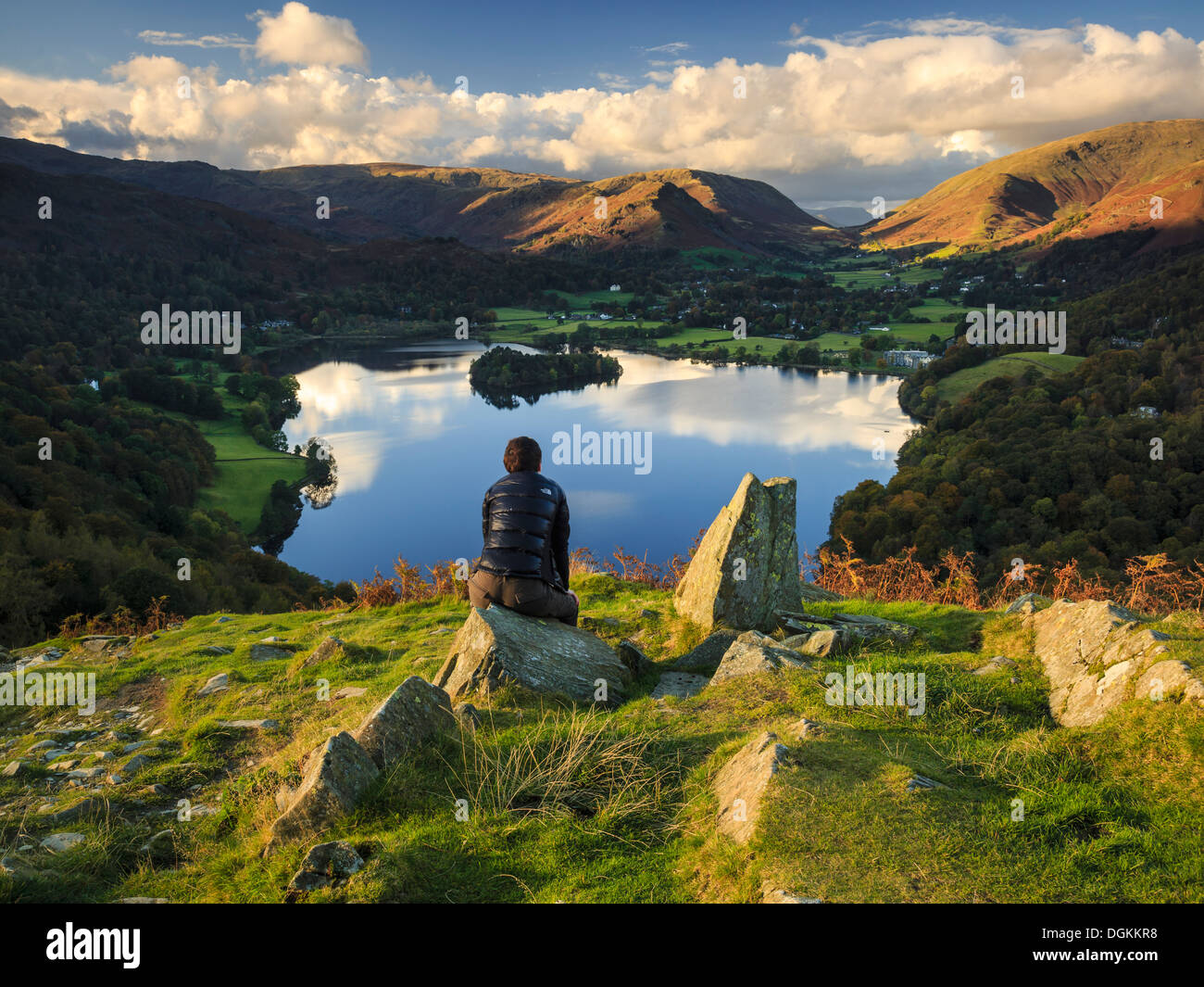 A walker admires the view of Grasmere from Loughrigg Hill - Stock Image