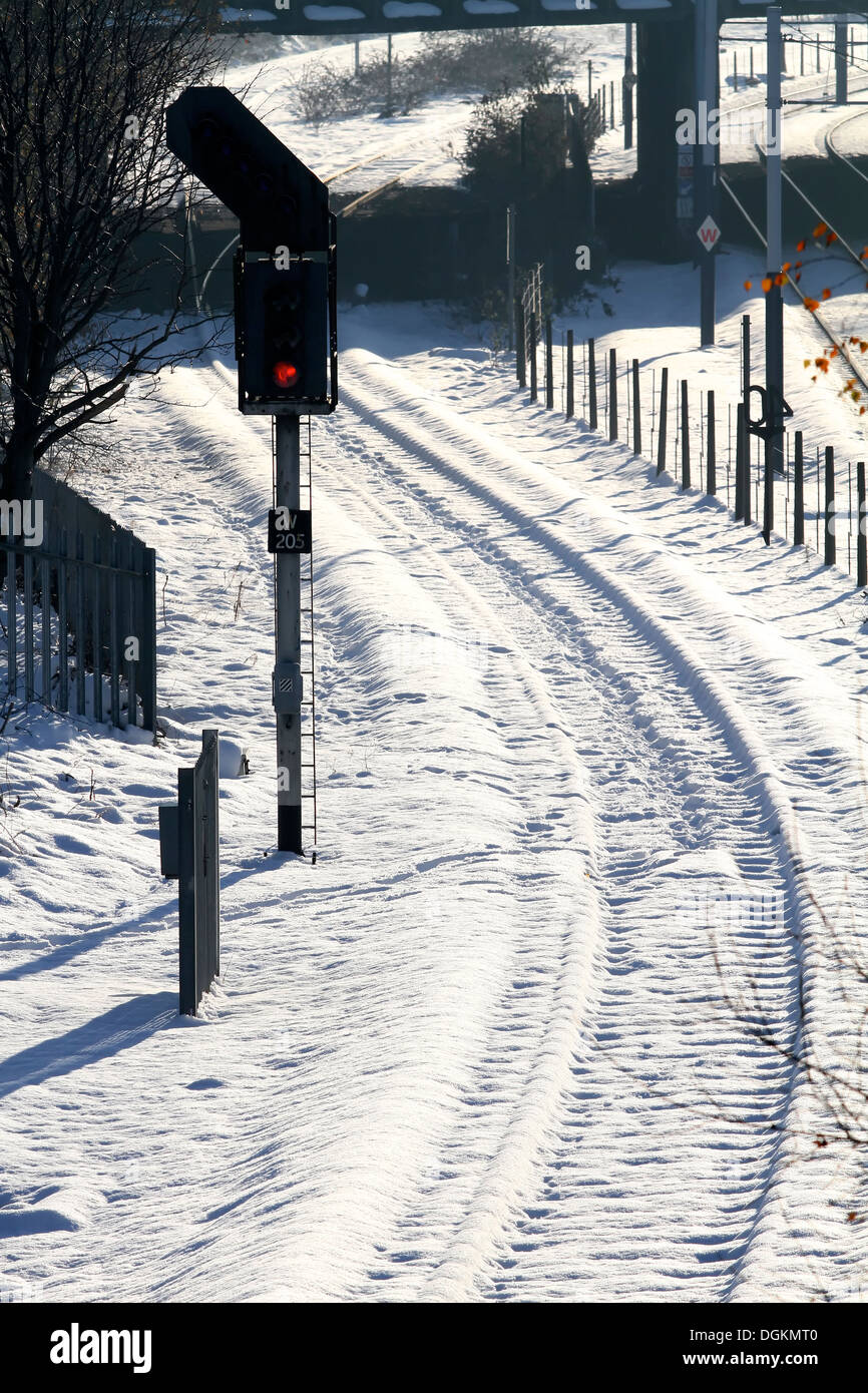 Curving railway lines completely covered in snow next to a red signal. - Stock Image