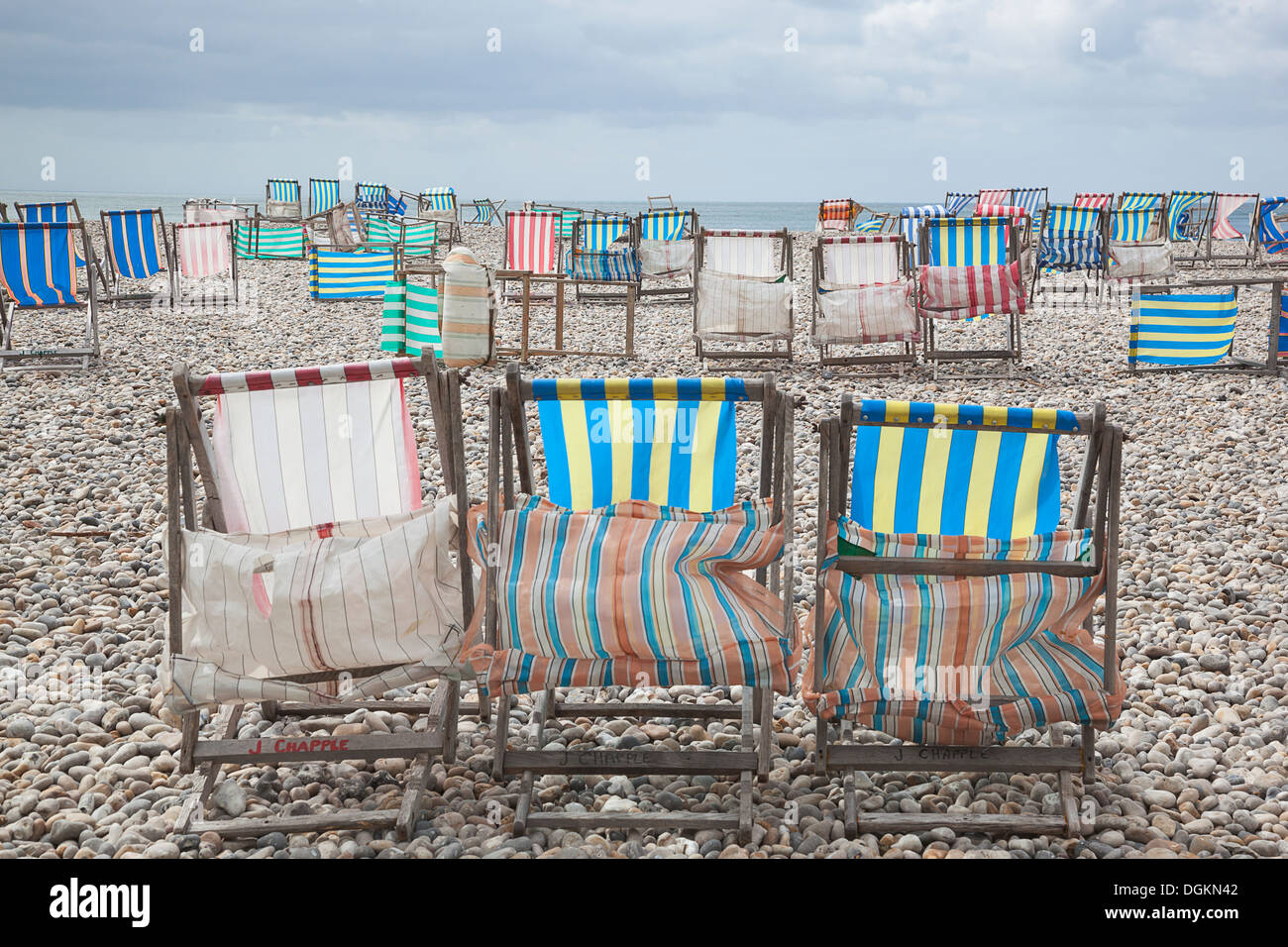 Deck chairs in high wind on the beach at Beer. - Stock Image