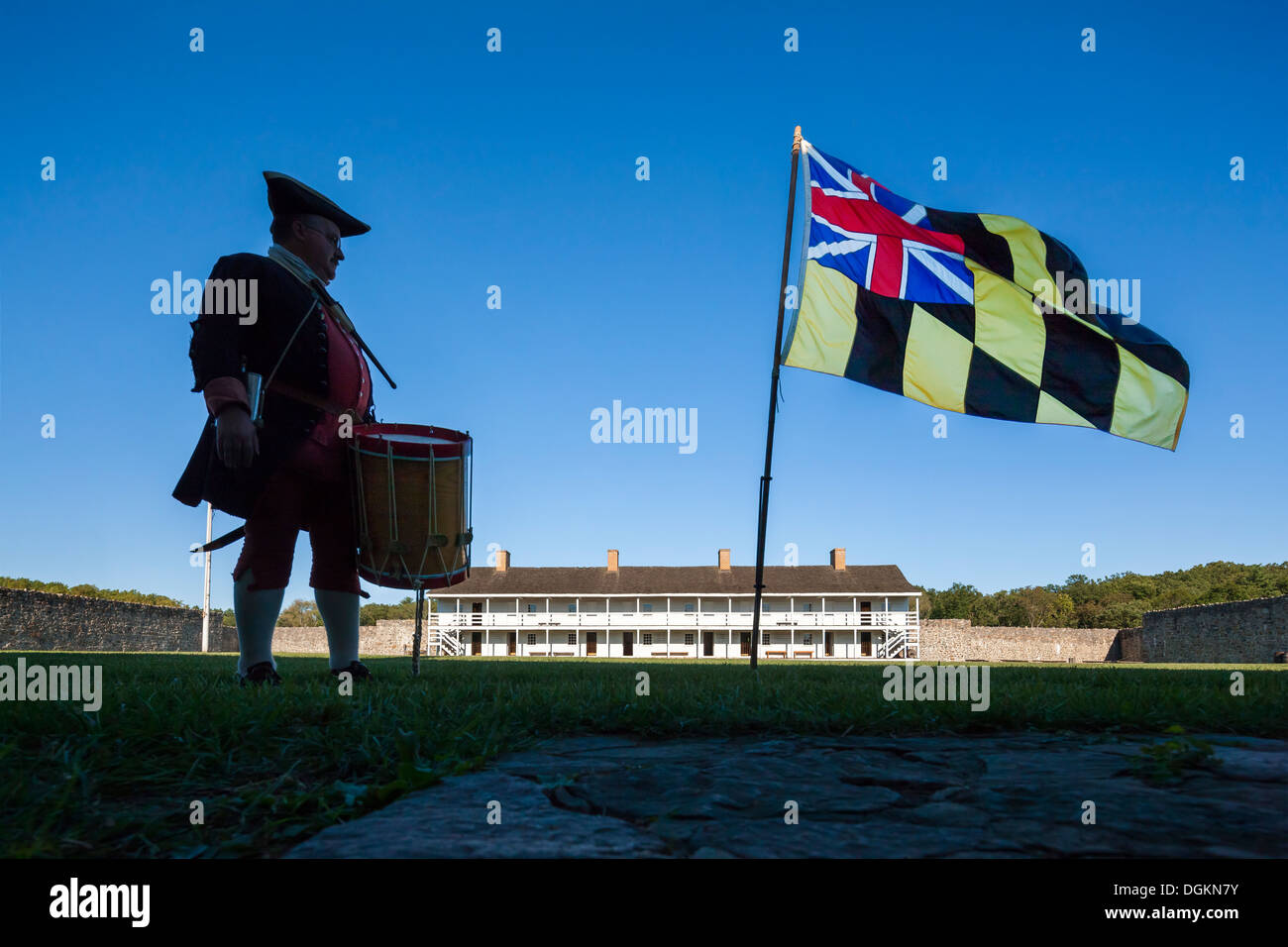 Historic daily life in Fort Frederick Maryland volunteer drummer with colonial era Maryland flag and East barracks. - Stock Image