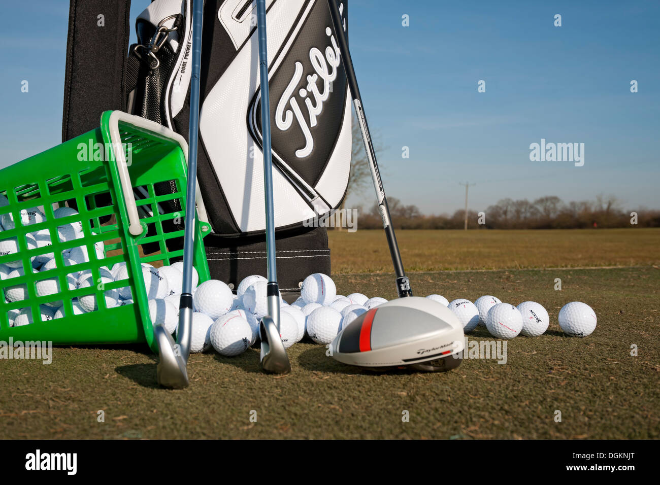 Golf clubs and golf balls on a driving range. Stock Photo