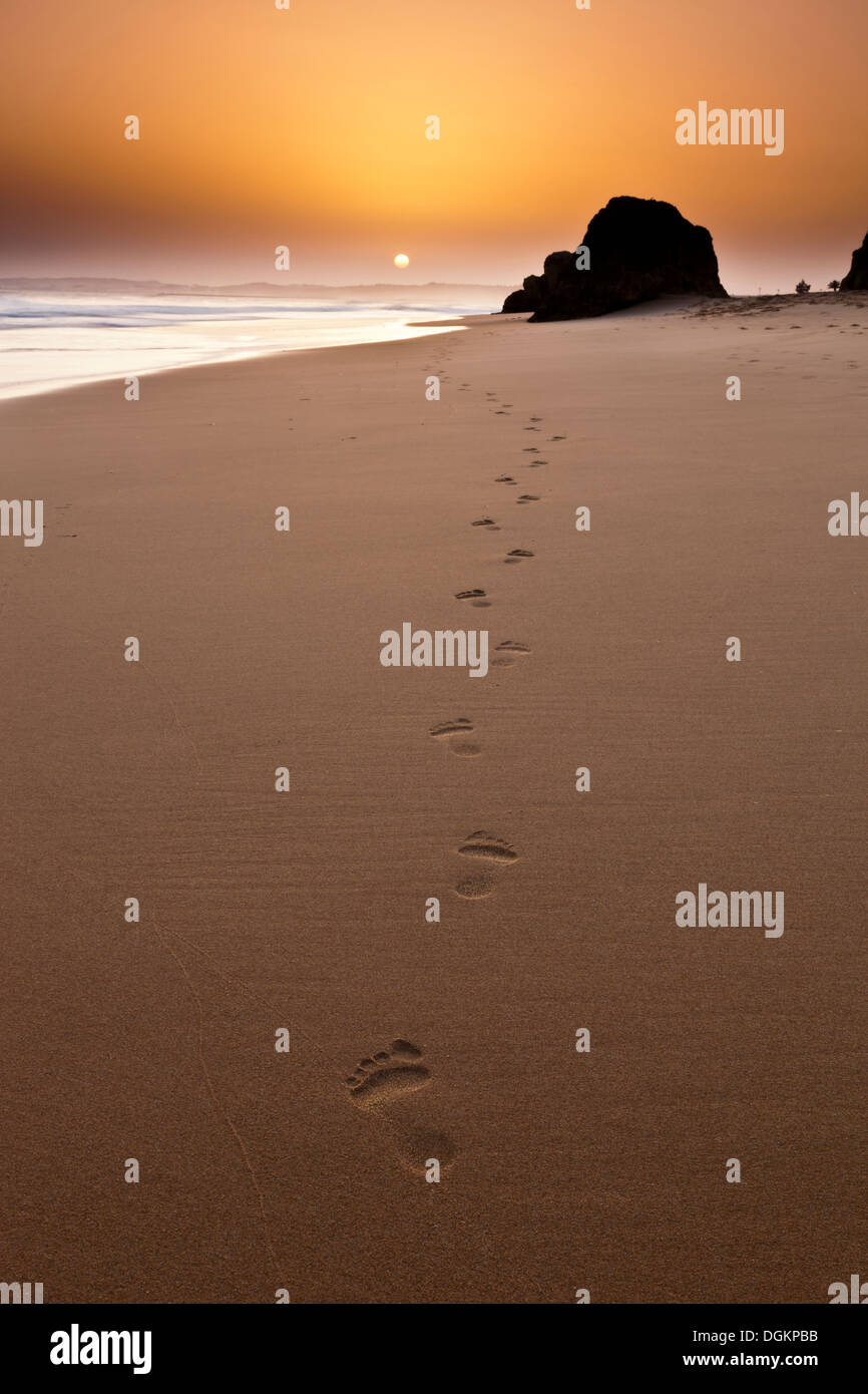 Footsteps left behind in the sand at sunset. - Stock Image