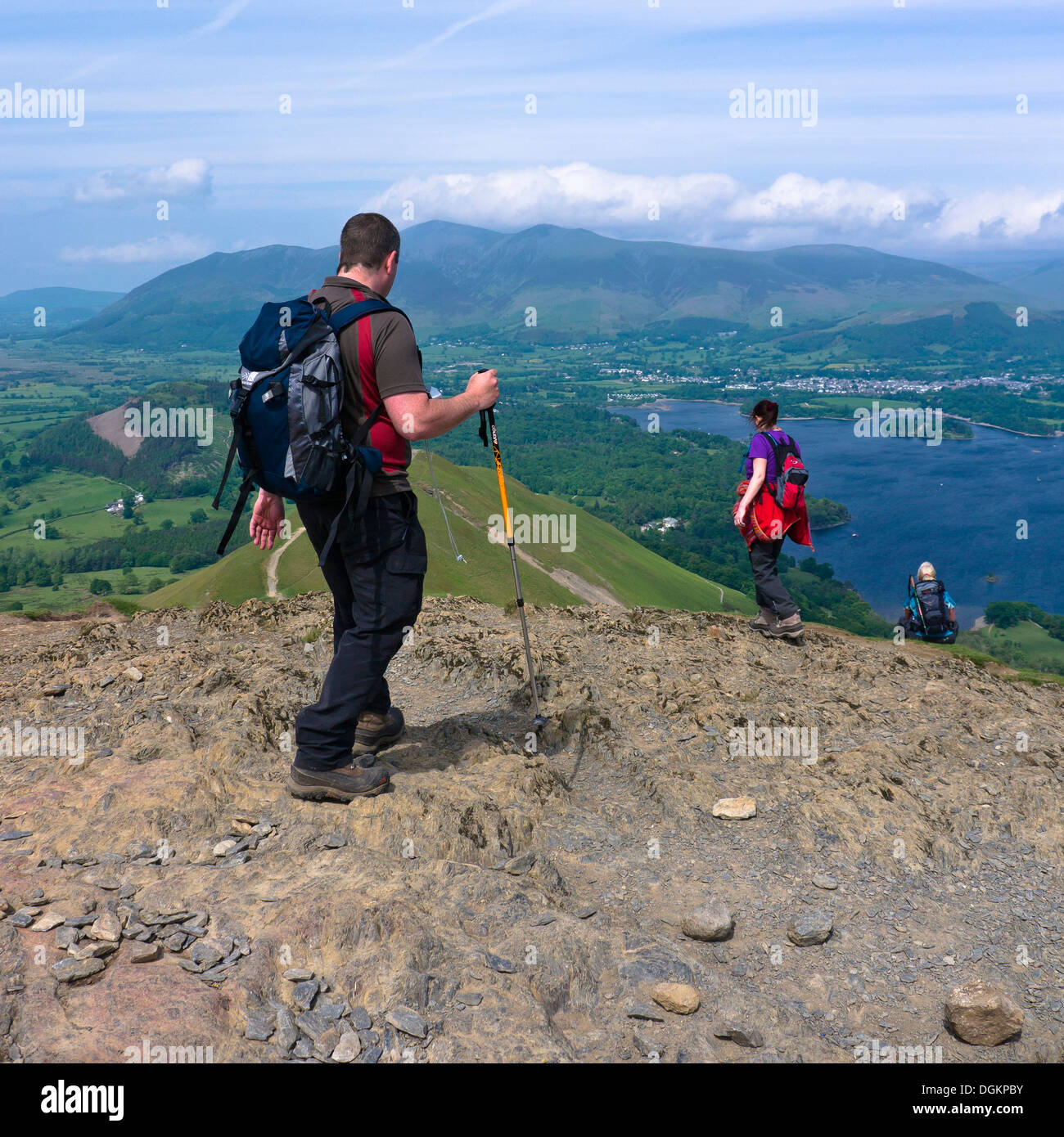 Three walkers descending from Catbells with Derwent Water in the distance. - Stock Image