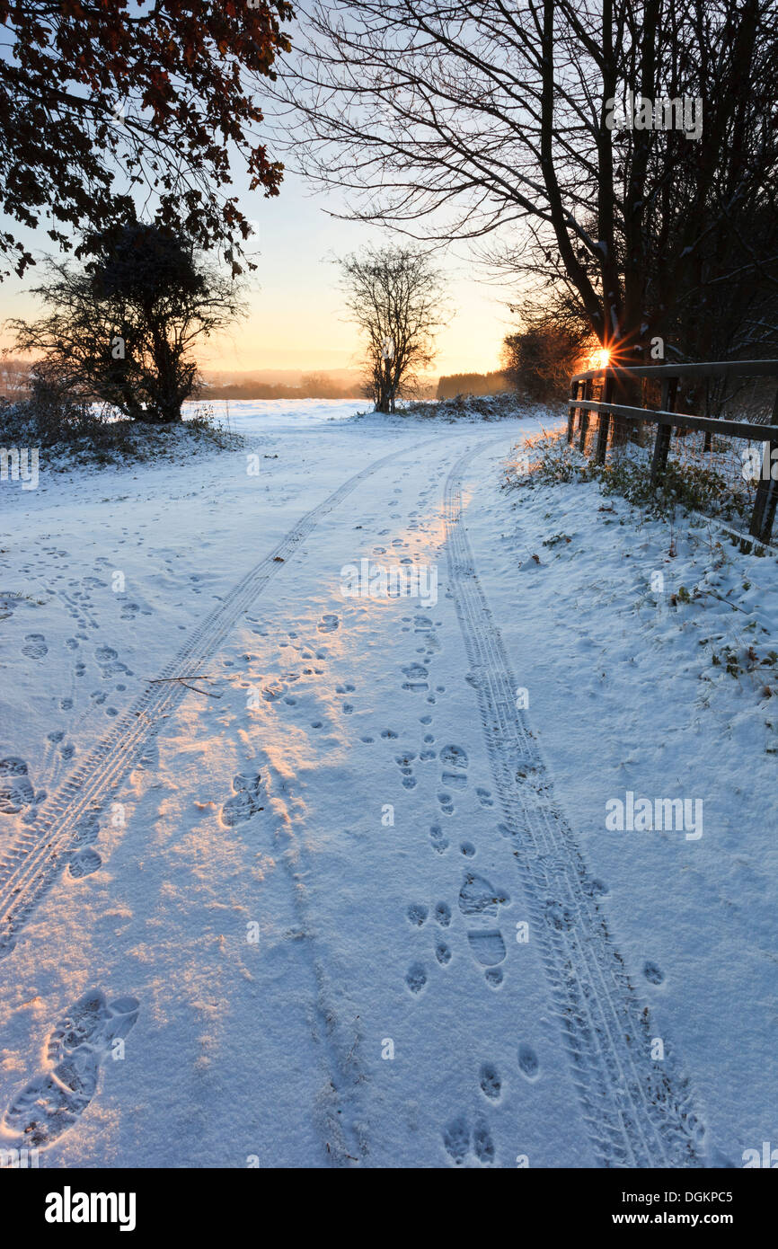 Tire tracks and footprints in the snow on a snowy winter morning. - Stock Image