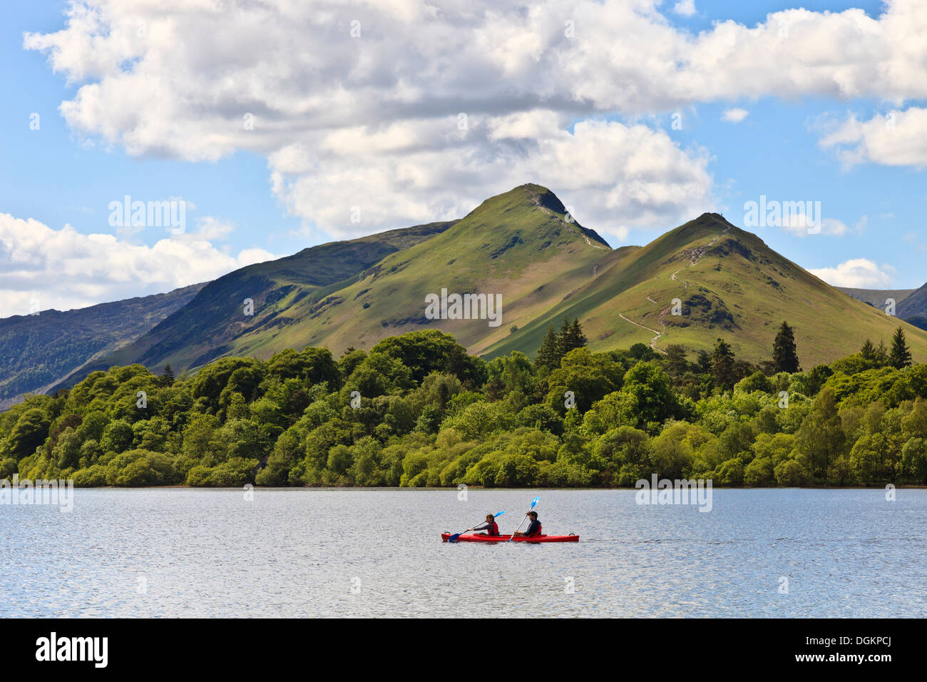 Two people paddle a red canoe on Derwent Water with Catbells in the background. - Stock Image