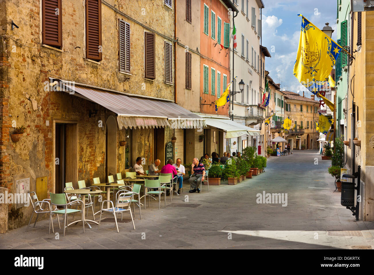 People sitting at tables outside the wine bar in Asciano. - Stock Image