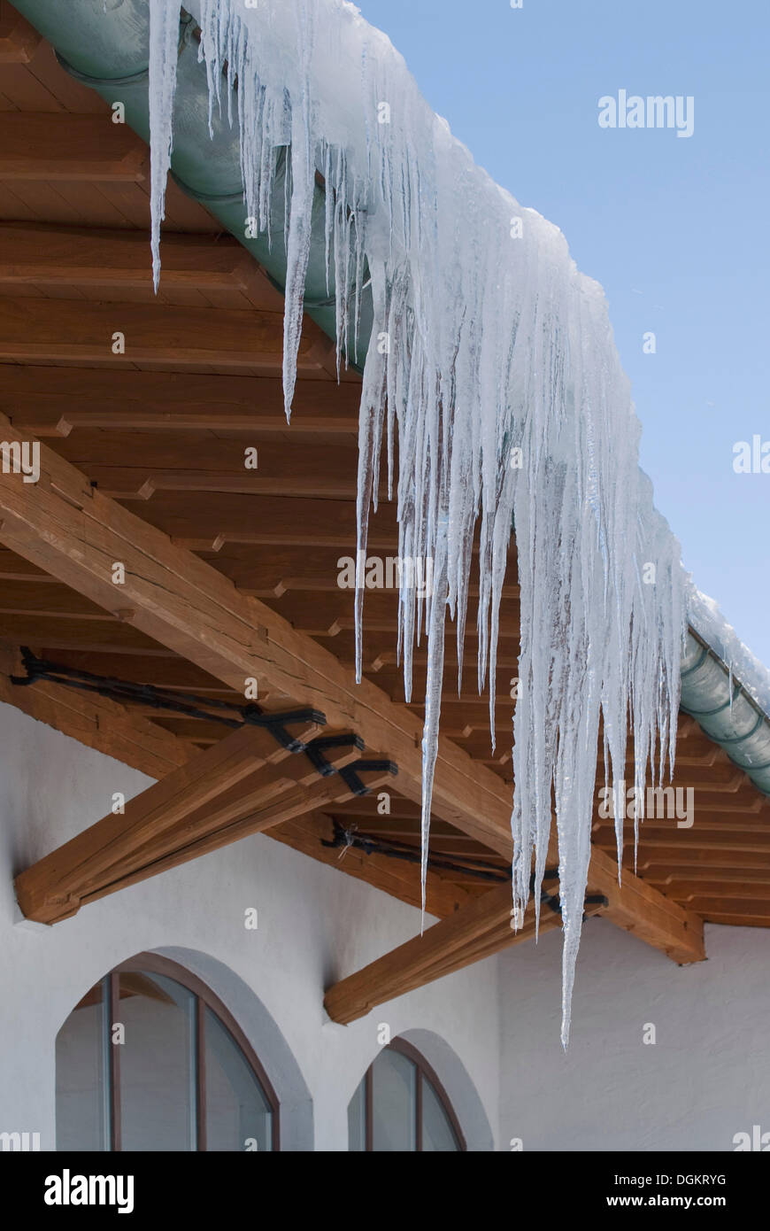 Big icicles hanging over the gutter of a mountain lodge, Bavaria - Stock Image