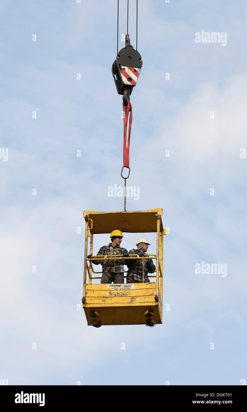 Workers standing inside the raised safety cage of a building crane, industrial safety, construction industry - Stock Image
