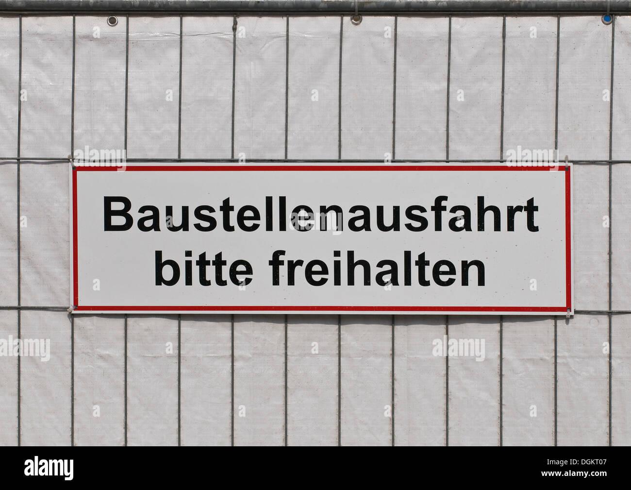 Sign on a fence, Baustellenausfahrt bitte freihalten, exit please keep clear - Stock Image