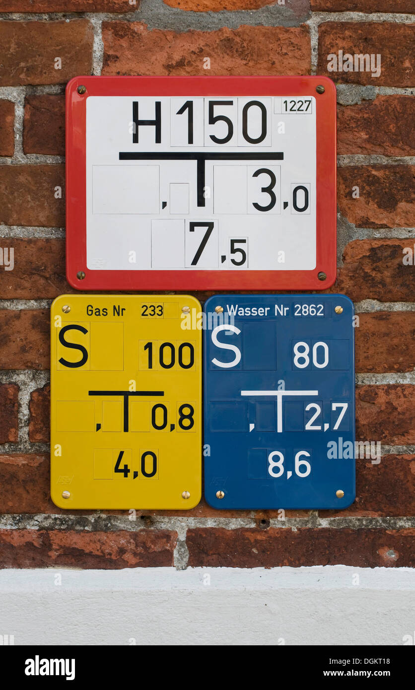 Different slider signs, fire-hydrant signs, gas and water, on brick wall - Stock Image