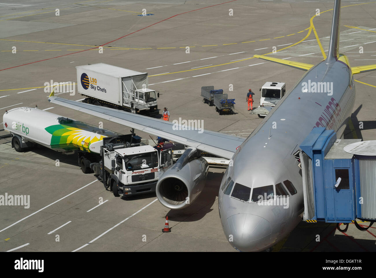 Airplane connected to a gangway, being refueled with service vehicles, apron, Cologne Bonn Airport, North Rhine-Westphalia - Stock Image