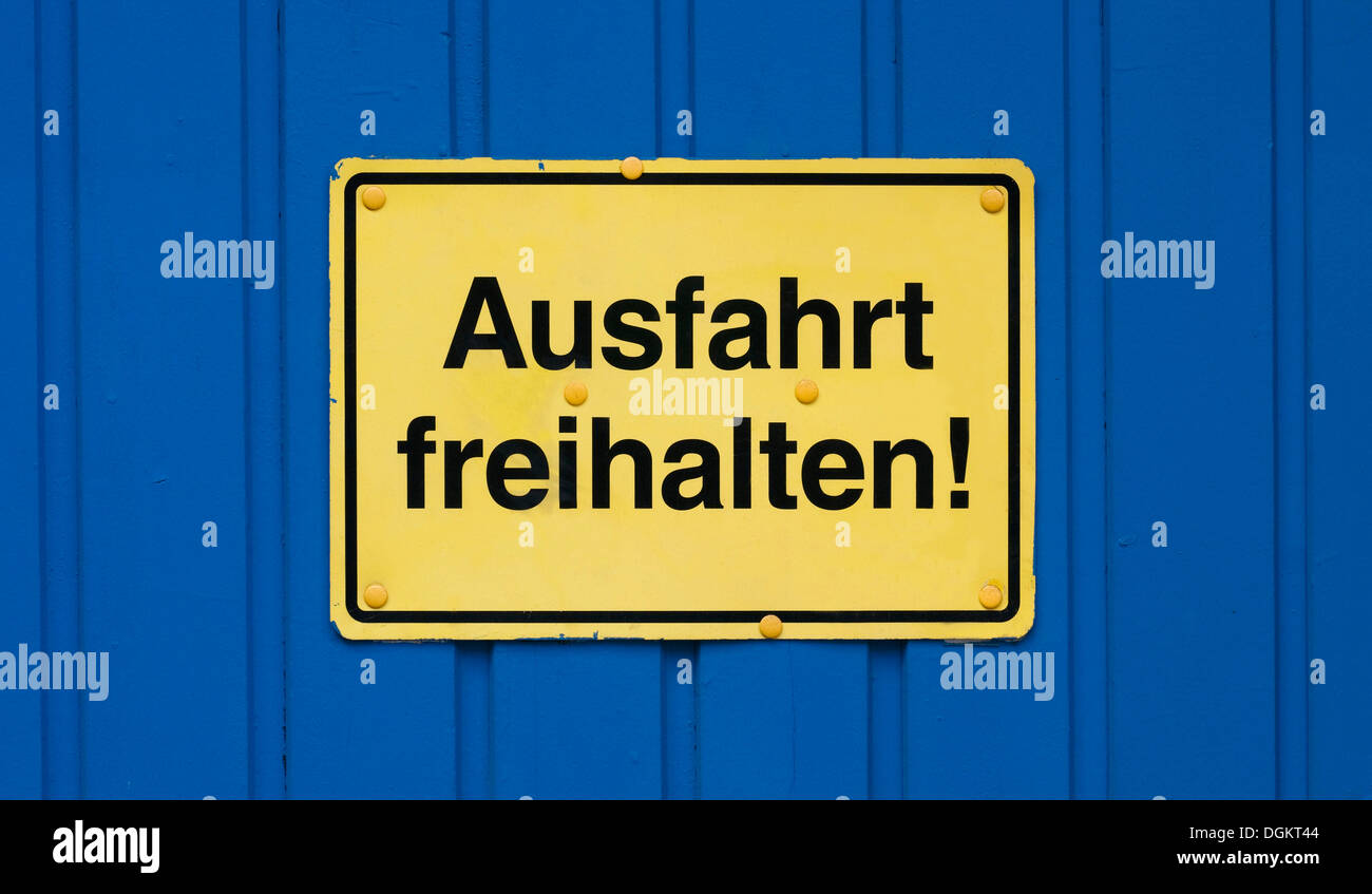 Sign, Ausfahrt freihalten or exit keep clear!, yellow on blue door - Stock Image