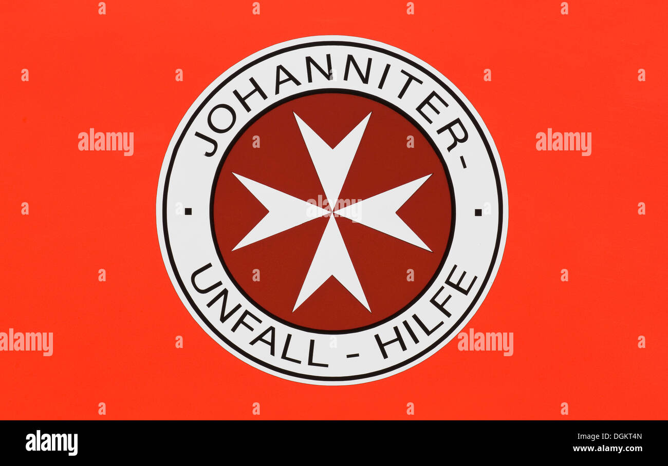 Logo of the Johanniter-Unfall-Hilfe, German for St. John Accident Assistance on a signal red base - Stock Image