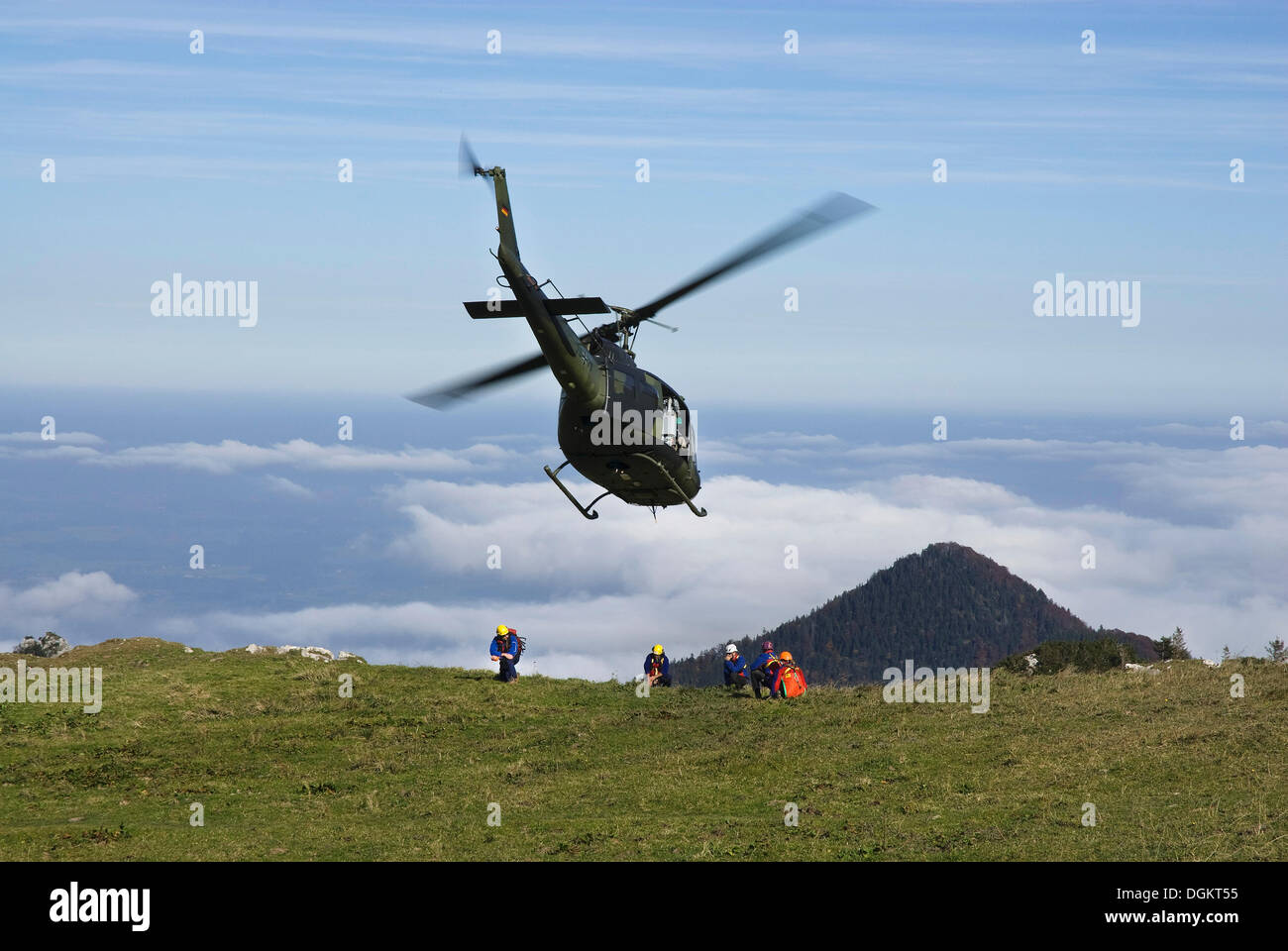 Helicopter being marshalled by rescue workers, German army helicopter in approach for landing, Chiemgau Alps, Bavaria - Stock Image