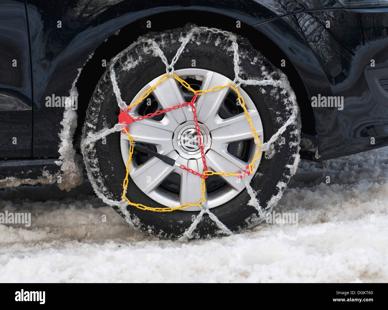 Car tyre with mounted snow chains in the snow - Stock Image