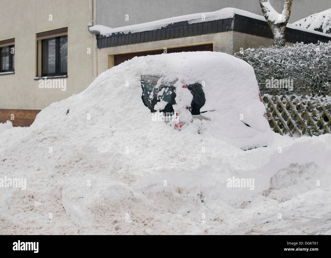 Snowed-in car at the roadside - Stock Image