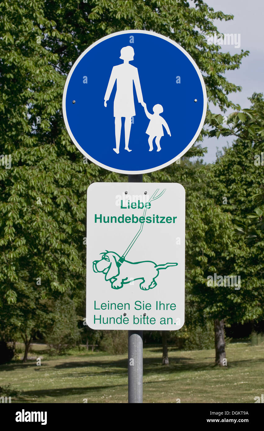Sign in a park: foot path, Liebe Hundebesitzer, Leinen Sie Ihre Hunde bitte an or dog owners, please keep your dog on a leash - Stock Image