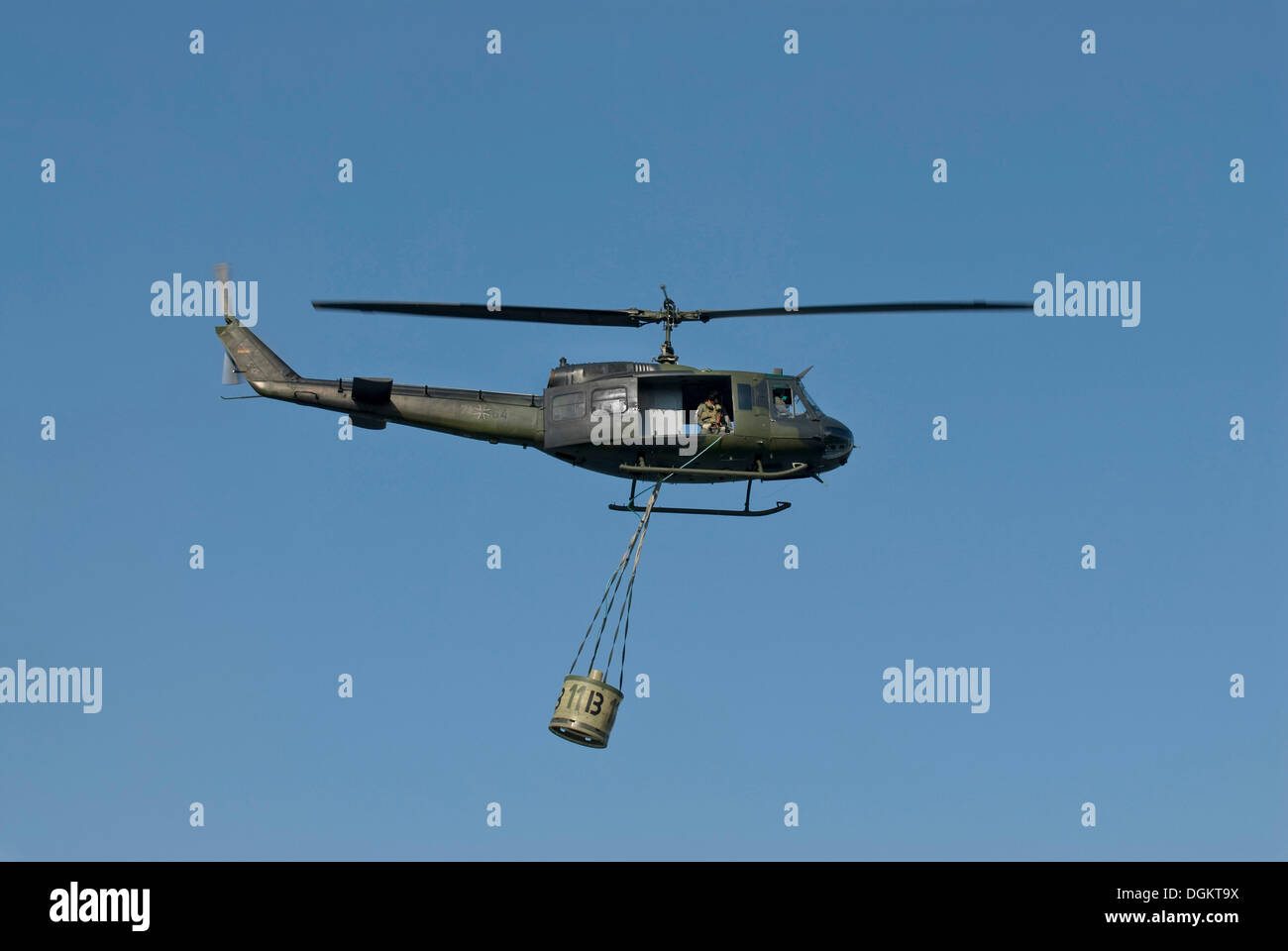 Bundeswehr, federal army, helicopter Bell UH-1D HUEY with water tank in fire-fighting operation, in flight, PublicGround - Stock Image