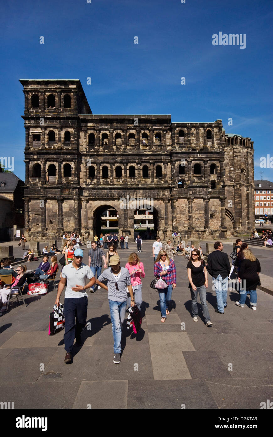 Young people strolling in front of the Porta Nigra, Trier landmark, UNESCO World Heritage Site, Rhineland-Palatinate - Stock Image