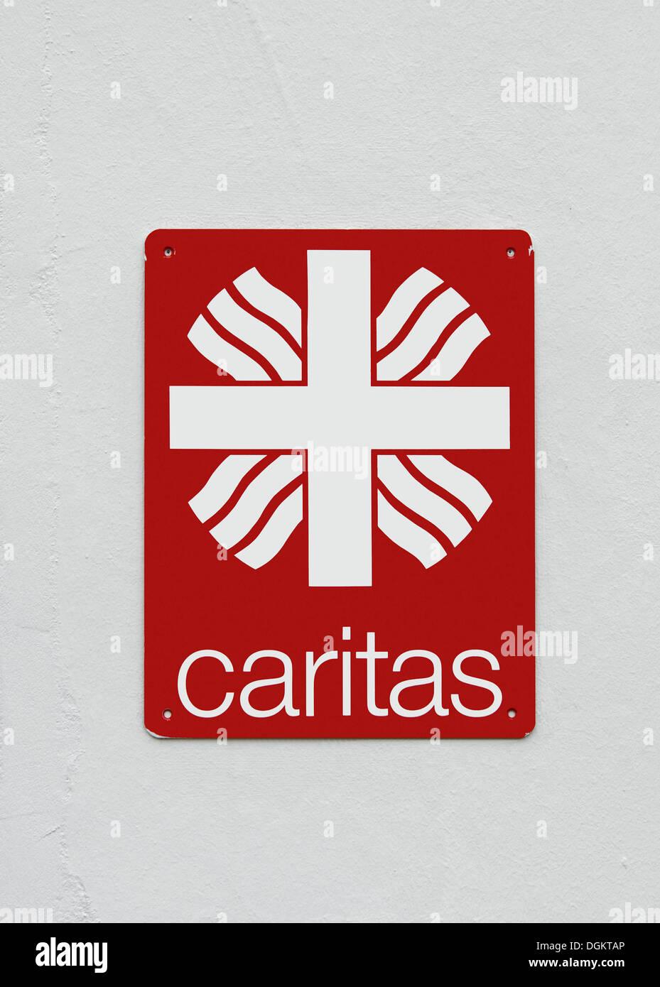 Sign, logo of Caritas, on a white wall, Deutscher Caritasverband e.V., Roman Catholic Caritas charity, PublicGround - Stock Image