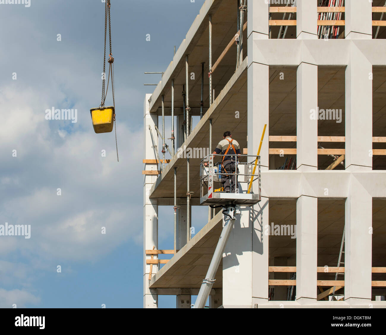 Workers in a lift at a construction site, a concrete vessel is being lowered from a crane, work safety, PublicGround - Stock Image