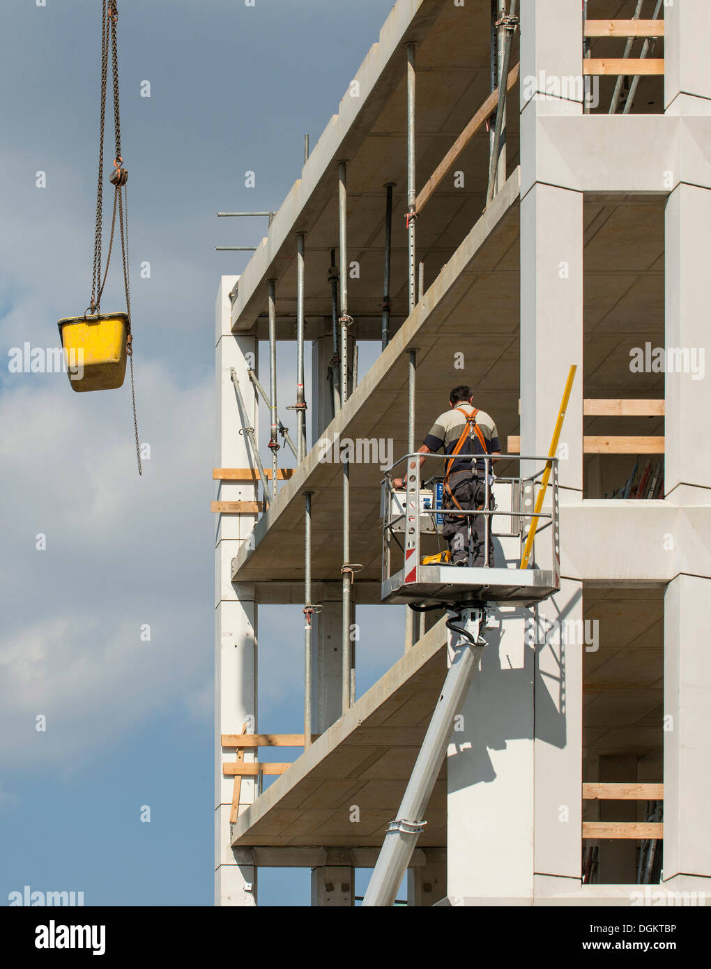 Workers in a lift at a construction site, a concrete tank is being lowered from a crane, work safety, PublicGround - Stock Image