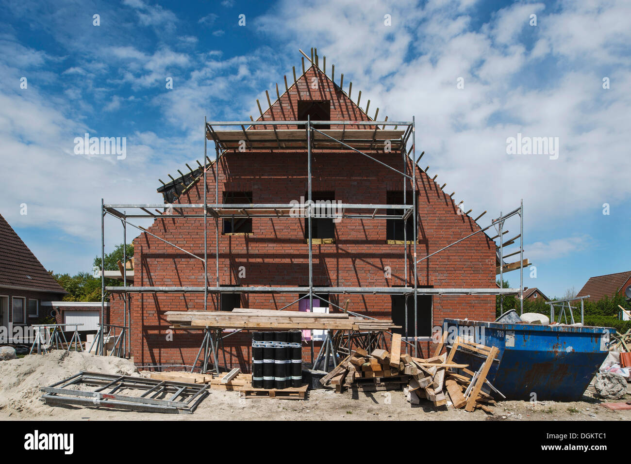 Scaffolded building, apartment house, piles of rubble and building materials at the front, Norden, East Frisia, Lower Saxony - Stock Image