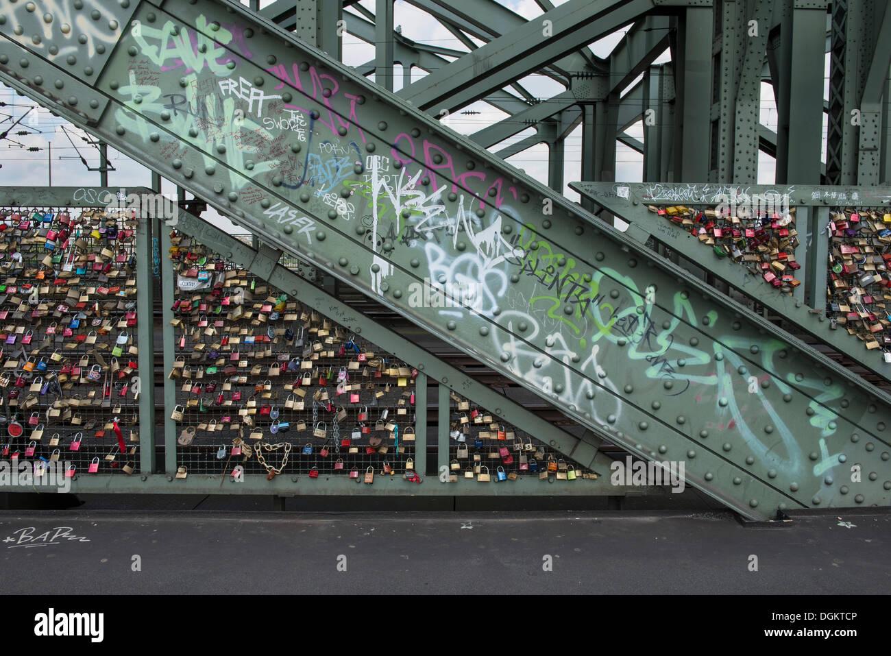 Hohenzollern Bridge, pillars with graffiti and fences full of love padlocks, Cologne, North Rhine-Westphalia - Stock Image